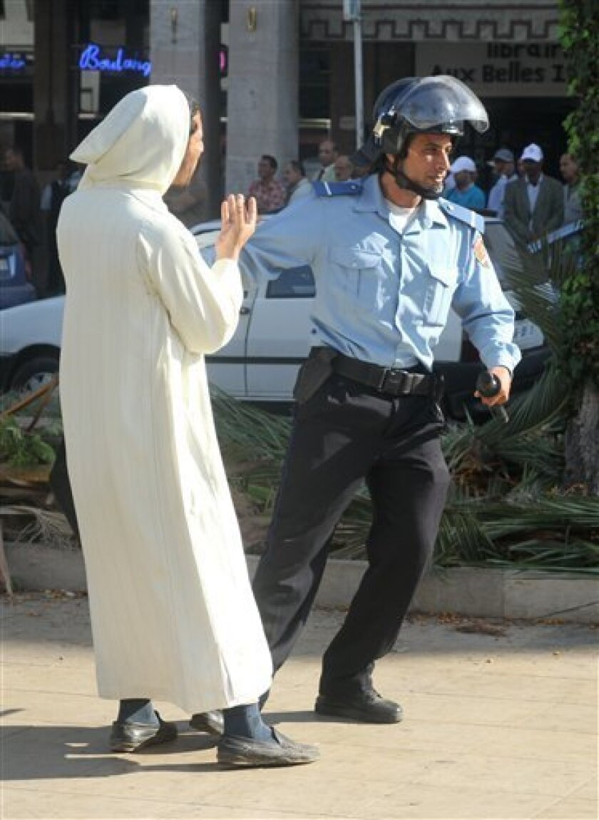 A police officer detains an imam during a protest in downtown Rabat, Morocco, Monday, Oct. 10, 2011. Dozens of imams from mosques across Morocco have protested in the capital over tight controls on their preaching. (AP Photo/Paul Schemm)