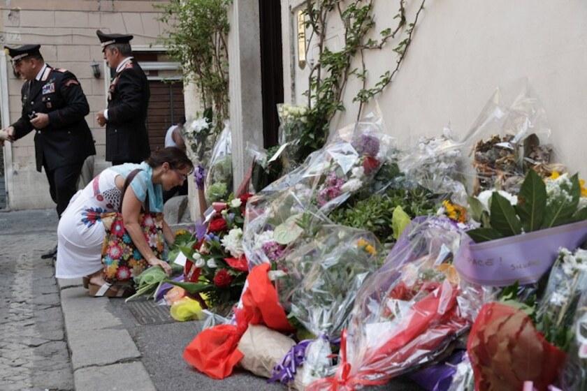 Una mujer coloca flores frente a la estación de policía en la que trabajaba el agente Mario Cerciello Rega. Dos estadounidenses de 19 años fueron arrestados como presuntos autores de la muerte a puñaladas del oficial.