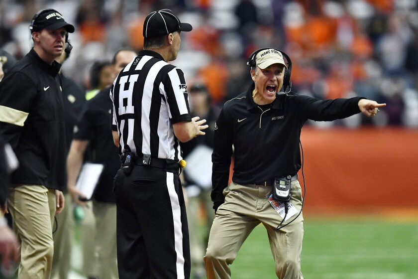 FILE - In this Saturday, Nov. 30, 2019, file photo, Wake Forest head coach Dave Clawson, right, speaks to an official during the second half of an NCAA college football game against Syracuse in Syracuse, N.Y. Wake Forest has been to four straight bowl games but will have to overcome significant personnel losses on offense in Clawson's seventh season. (AP Photo/Adrian Kraus, File)
