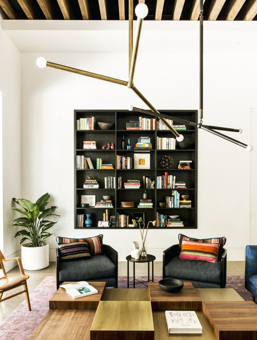 A statement-making stained wood bookshelf built into the wall in the sitting area of the Sinegal Est
