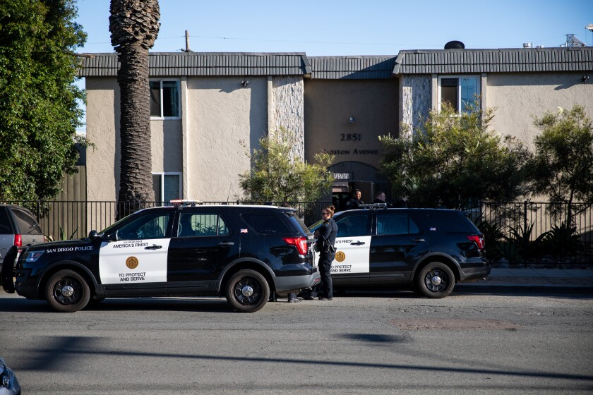 Police vehicles are seen outside the apartment complex on Boston Avenue in Barrio Logan where a woman was killed.