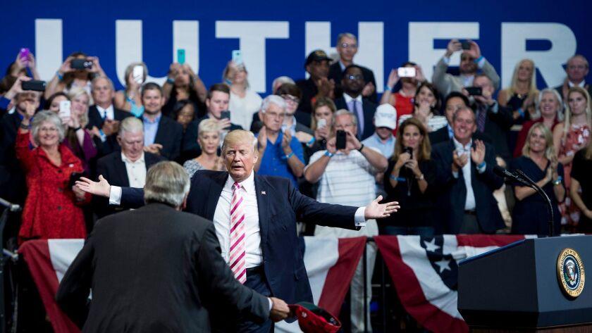 President Trump is greeted by Alabama Sen. Luther Strange at the Von Braun Civic Center in Huntsville.
