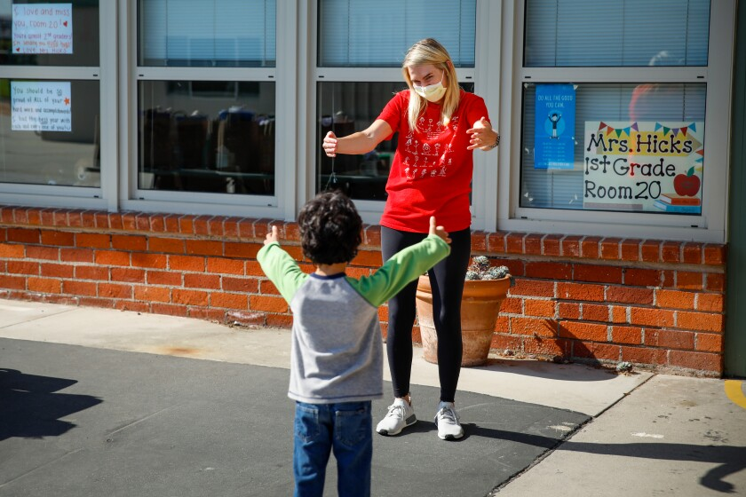 First-grade teacher Caitlin Hicks gives an air hug to Sid Solomon