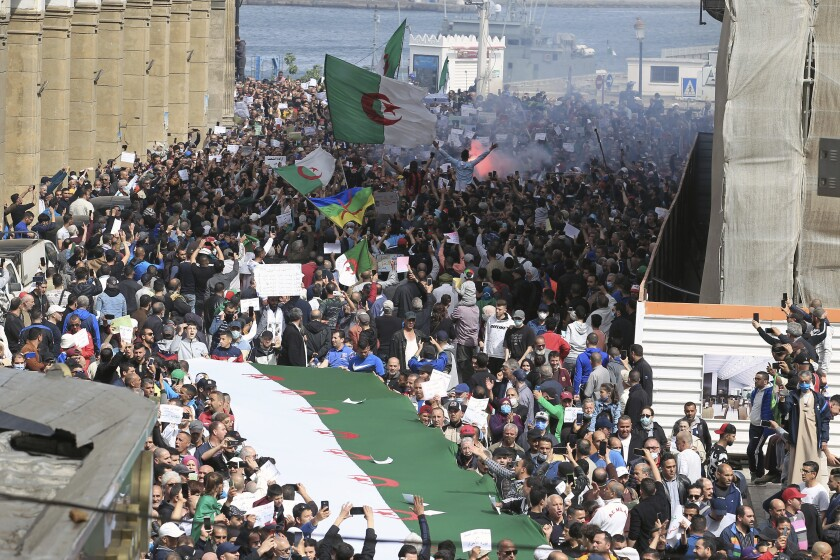 Demonstrators take the street of Algiers, Friday, April 2, 2021. A crowd of protesters marched peacefully in the streets of Algeria capital Algiers in support for the Hirak pro-democracy movement. Tens of thousands of students and older people headed in the city center toward the imposing central post office, the traditional rallying point for the movement, in a joyful atmosphere. (AP Photo/ Fateh Guidoum)
