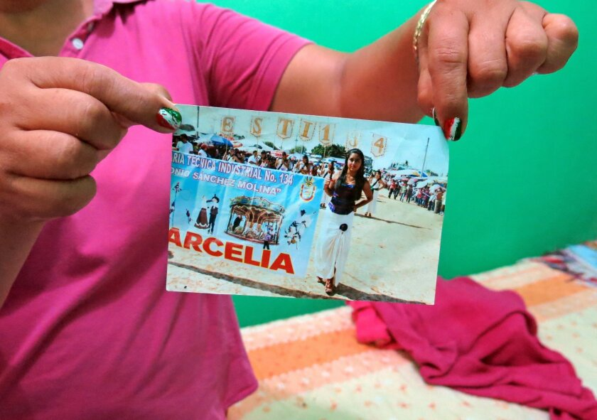 In this Sept. 15, 2014 photo, a woman who did not want to give her name for fear of reprisals, holds up a photograph of her late 15-year-old daughter Erika Gomez Gonzalez, at her home in Arcelia, Mexico. The woman says she witnessed her child's death when army soldiers fired first at an armed group