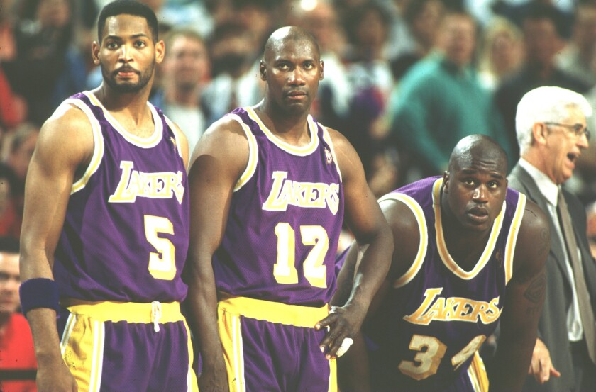 Jerome Kersey (12) watches from the sideline with Lakers teammates Robert Horry (5) and Shaquille O'Neal (34) during the 1996-97 season.