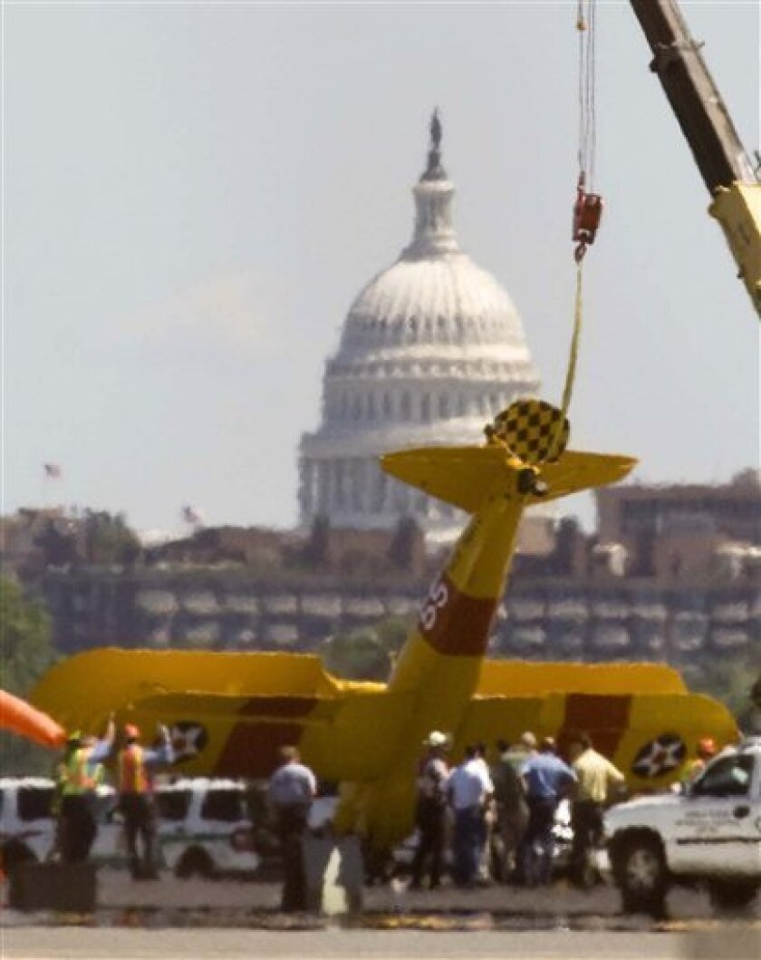 Workers use a crane to lift a vintage plane that crashed while landing at Washington's Ronald Reagan National Airport, Tuesday, June 8, 2010. (AP Photo/Kevin Wolf)