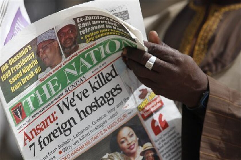 A man reads a local newspapers with the headline 'We've killed 7 foreign hostages' on a street in Kano, Nigeria, Sunday, March. 10, 2013. The United Kingdom's military says its warplanes recently spotted in Nigeria's capital city were there to move soldiers to aid the French intervention in Mali, not to rescue kidnapped foreign hostages. The Ministry of Defense said Sunday that the planes had ferried Nigerian troops and equipment to Bamako, Mali. An Islamic extremist group in Nigeria called Ansa