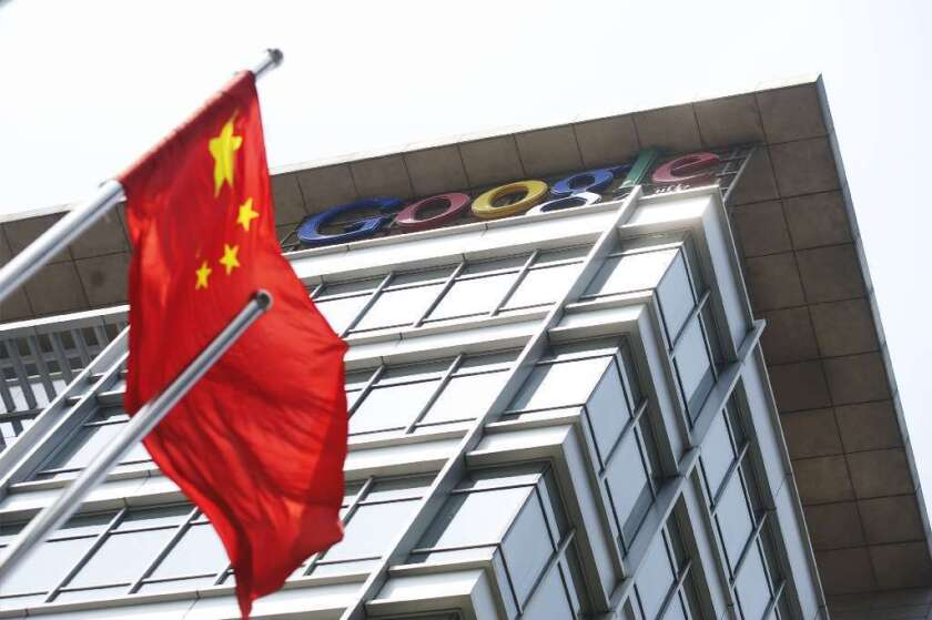 The Obama administration charged five Chinese officials with hacking into U.S. companies. Above, a Chinese flag blows in the wind in front of Google Inc.'s offices in Beijing.