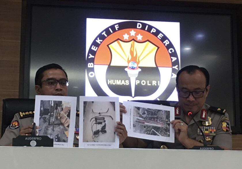 Indonesian National Police spokesperson Brig.Gen. Dedi Prasetyo, right, and an aide show photos of evidence of confiscated items during raids following a knife attack against Indonesian Coordinating Minister for Politics, Law and Security Wiranto during a press conference in Jakarta, Indonesia, Monday, Oct. 14, 2019. Prasetyo says tens of suspected militants plotting bombings and other attacks have been arrested in a new counterterrorism crackdown since last week's brazen assault by a knife-wielding militant couple who wounded the country's top security minister in a western province. (AP Photo/Niniek Karmini)