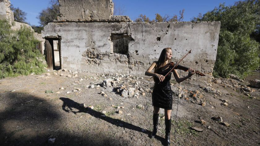 Amy Serrano Burcombe plays the electric violin with the backdrop of the Maxcy Winery ruins, circa 1852, at Rancho Guejito, one of the stops on the Rancho Guejito Vineyard wine-tasting tour that will soon be offered to the public.