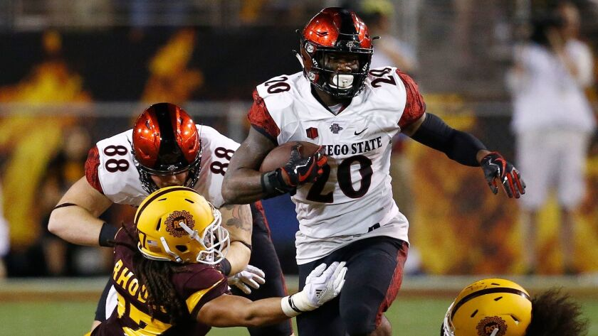 San Diego State's Rashaad Penny (20) runs with the ball as Arizona State's J'Marcus Rhodes, left, an
