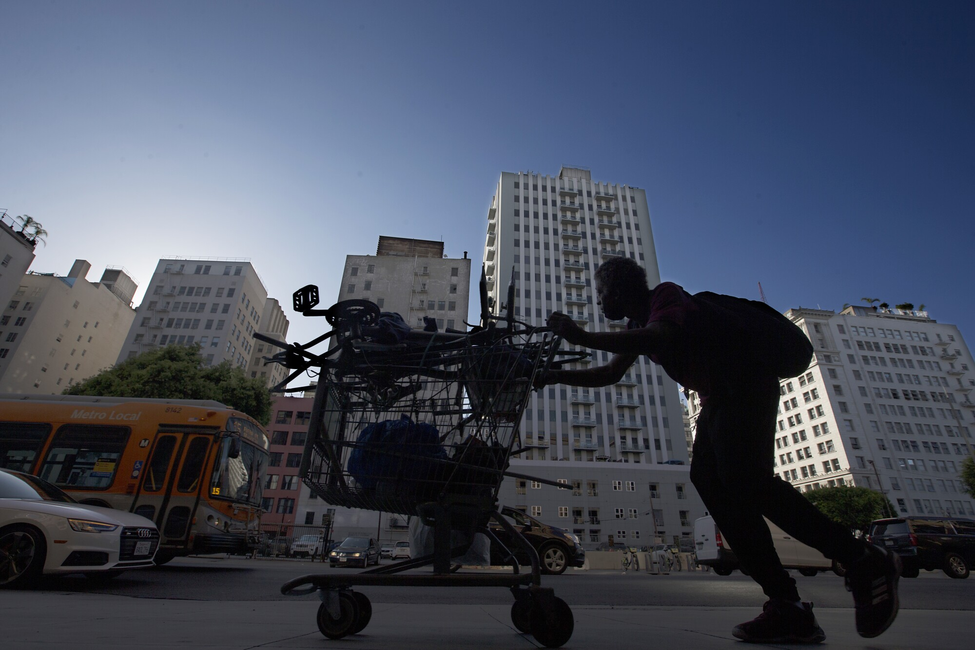 A man pushes a shopping cart along the sidewalk in the historic urban core of Los Angeles.