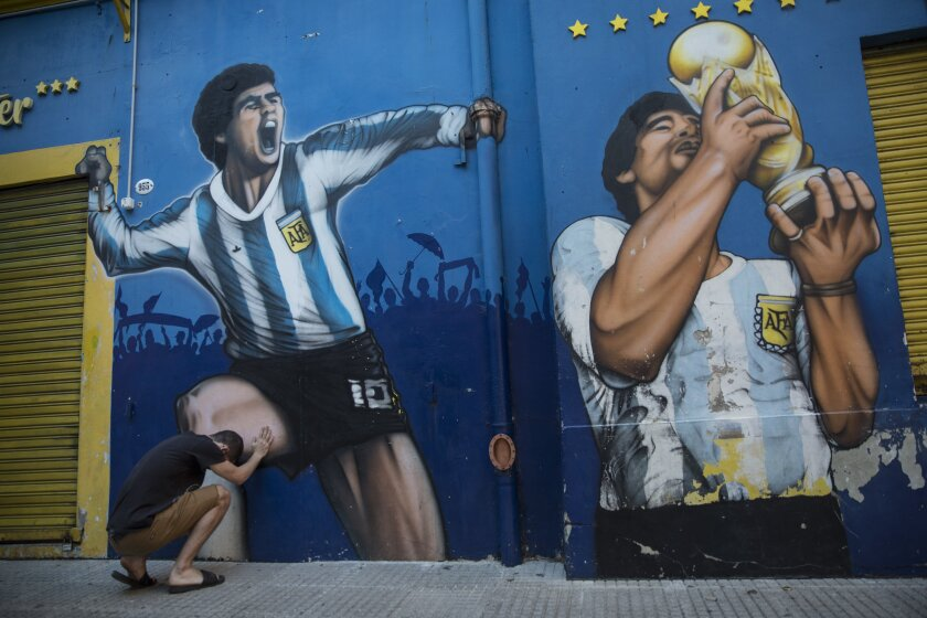 Augusto Canosa reza al tocar una pintura de Diego Maradona cerca del estadio La Bombonera