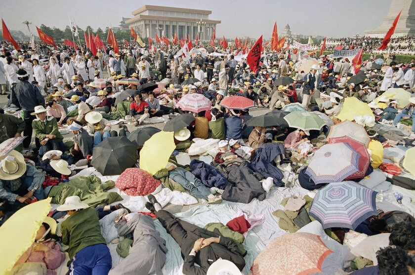 FILE - In this May 16, 1989 file photo, Beijing University students relax in Tiananmen Square as their hunger strike for democracy begins its fourth day in Beijing. The legacy of the 1989 crackdown in Tiananmen Square looms larger in Hong Kong than in mainland China, where the Communist Party has virtually erased all public mention of it. In this former British colony, hundreds of thousands attend candlelight vigils each anniversary to commemorate the grim end to the Beijing movement that was vanquished before many of the pro-democracy protesters in Hong Kong's streets were even born. (AP Photo/Sadayuki Mikami, File)