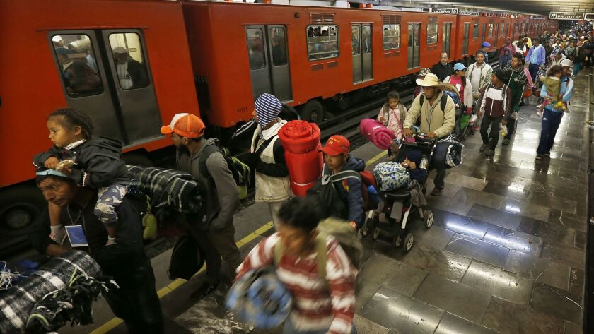 Central American migrants stand waiting for a subway car after leaving the temporary shelter at the