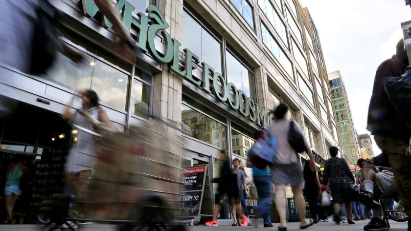 Pedestrians pass in front of a Whole Foods Market store in Union Square, Wednesday, June 24, 2015, i