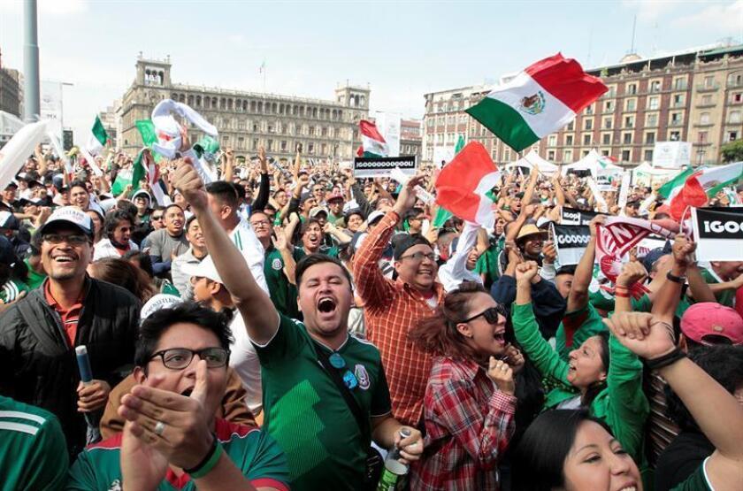 Aficionados de México celebran la clasificación a octavos de final de su equipo durante la transmisión del partido del Mundial de Rusia 2018 entre México y Suecia hoy, miércoles 27 de junio de 2018, en el Zócalo de Ciudad de México (México). EFE