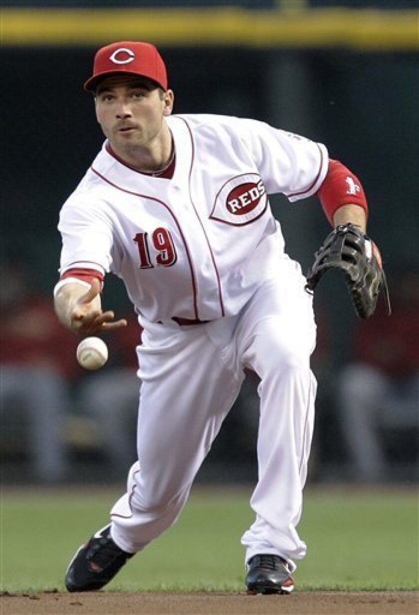 Cincinnati Reds first baseman Joey Votto tosses the ball to pitcher Edinson Volquez after fielding a ground ball hit by Houston Astros' Hunter Pence in the first inning of a baseball game, Tuesday, Sept. 28, 2010, in Cincinnati. Pence was safe at first base. (AP Photo/Al Behrman)