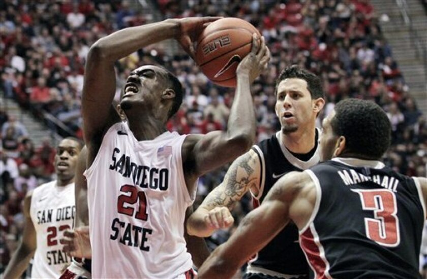 San Diego State's Jamaal Franklin (21) goes up for a shot as UNLV's Anthony Marshall (3) and Carlos Lopez, second from right, defend during the first half pf an NCAA college basketball game Saturday, Jan. 14, 2012, in San Diego. (AP Photo/Gregory Bull)
