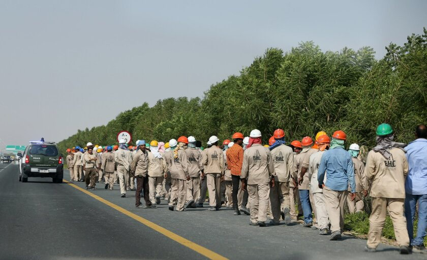 Migrant laborers walk during a protest near the airport hosting the biennial Dubai Airshow in the United Arab Emirates, Sunday, Nov. 8, 2015. Hundreds of migrant laborers have staged a protest near the airport hosting the biennial Dubai Airshow. Associated Press journalists saw the workers gatherin
