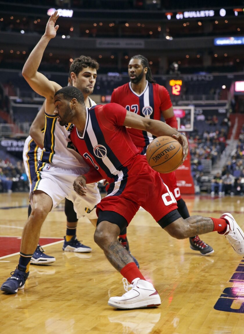 Washington Wizards guard John Wall (2) drives against Utah Jazz guard Raul Neto, from Brazil, during the first half of an NBA basketball game Thursday, Feb. 18, 2016, in Washington. (AP Photo/Alex Brandon)
