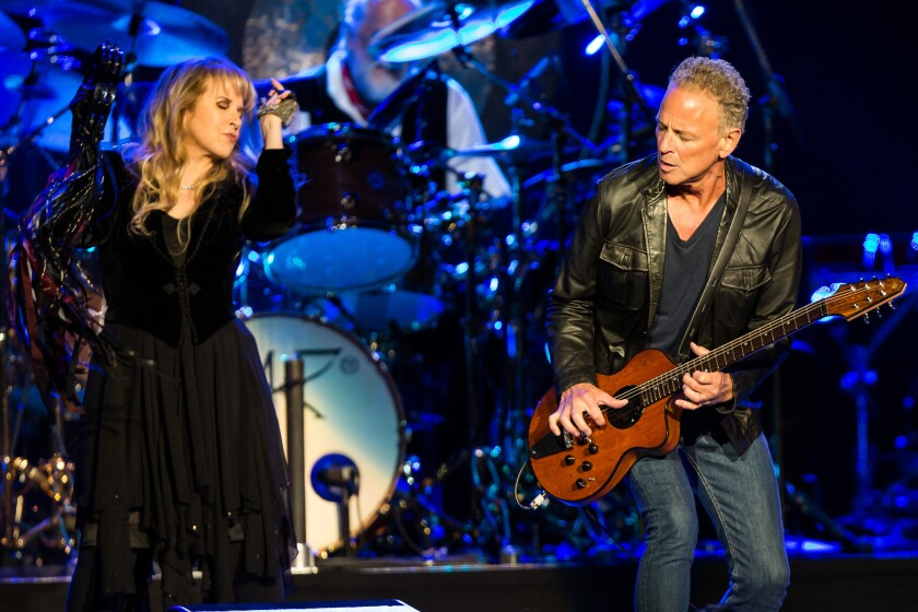 A woman and a man with a guitar perform together onstage