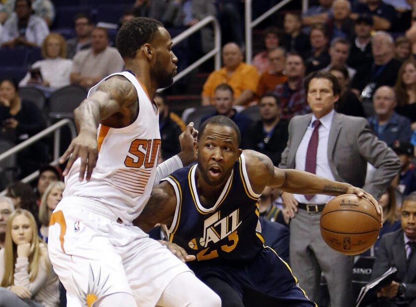Utah Jazz forward Chris Johnson (23) drives on Phoenix Suns guard Jordan McRae in the second quarter during an NBA basketball game, Saturday, Feb. 6, 2016, in Phoenix. (AP Photo/Rick Scuteri)