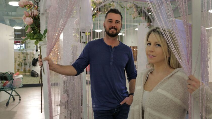 "Married co-owners Kyle Hill and Ann Delaney of La Costa inside the gazebo exhibit of their newly opened pop-up exhibit ""The Museum of What? Love Tour"" in Encinitas."