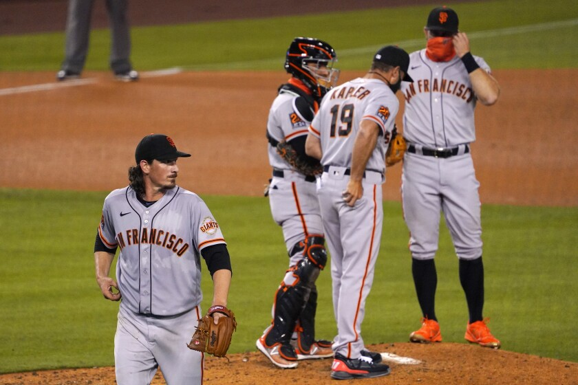 San Francisco Giants starting pitcher Jeff Samardzija, left, walks off the field after being taken out of the game during the fifth inning of a baseball game against the Los Angeles Dodgers Friday, Aug. 7, 2020, in Los Angeles. (AP Photo/Mark J. Terrill)