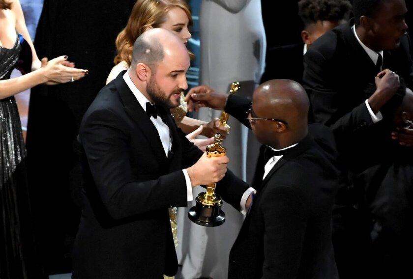 """La La Land"" producer Jordan Horowitz hands the best picture Oscar to ""Moonlight"" filmmaker Barry Jenkins."