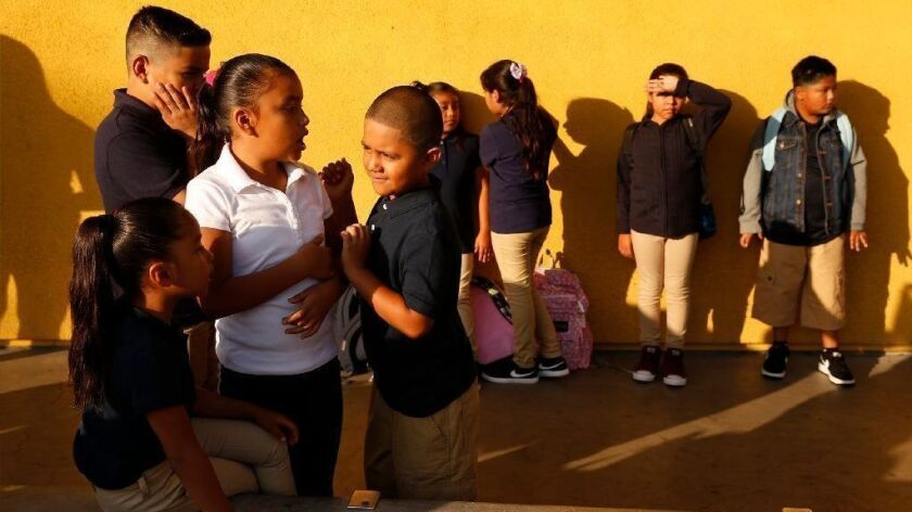 Third-graders wait for the doors to open on the first day of school at Dolores Huerta Elementary School in Los Angeles on Aug. 14.