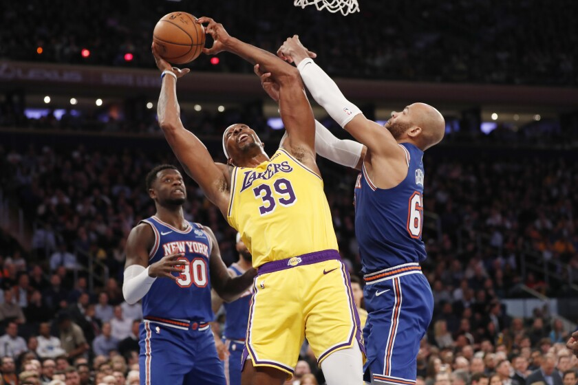 Lakers center Dwight Howard pulls down a rebound against Knicks forwards Taj Gibson, right, and Julius Randle during the first half of a game Jan. 22, 2020, in New York.