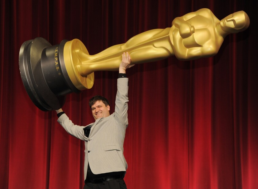 """Filmmaker John Mattiuzzi of the School of Visual Arts in New York, a nominee in the Alternative Category for his film """"The Compositor,"""" hoists up an Oscar statue for photographers before the Academy of Motion Picture Arts and Sciences 40th Student Academy Awards at the Samuel Goldwyn Theater."""