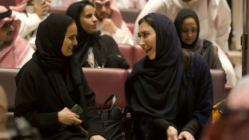 Visitors laugh as they attend a cinema theatre at an invitation-only screening, at the King Abdullah