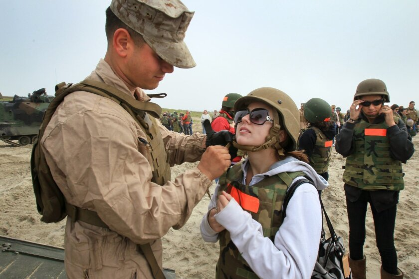 Lance Cpl. Kevin Cruz assists his wife Crystal with her helmet before getting on his amphibious assault vehicle for a ride on the beach.