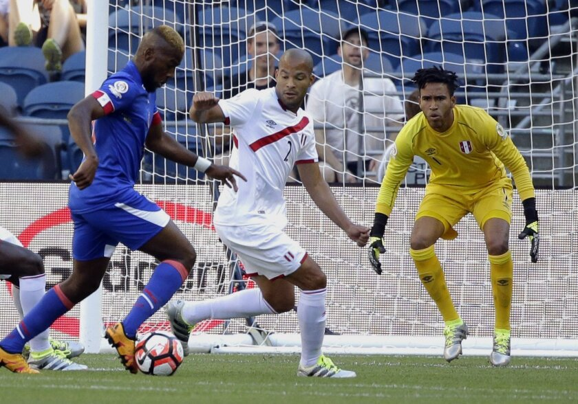 Peru goalkeeper Pedro Gallese, right, and defender Alberto Rodriguez, center, watch as Haiti forward Duckens Nazon, left, attempts a shot in the first half of a Copa America Centenario soccer match Saturday, June 4, 2016, in Seattle. (AP Photo/Ted S. Warren)