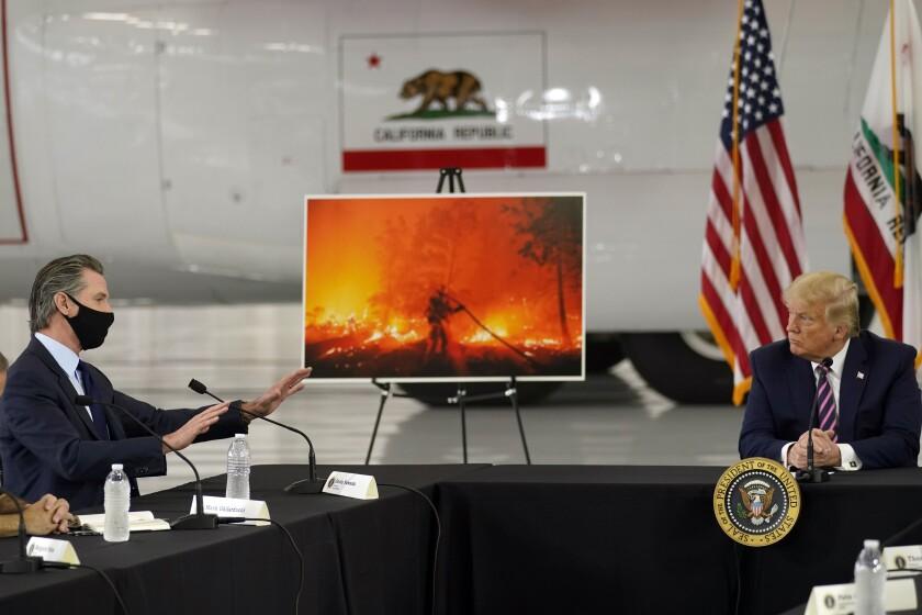 President Donald Trump listens as California Gov. Gavin Newsom speaks during in McClellan Park, Calif., Monday, Sept. 14.