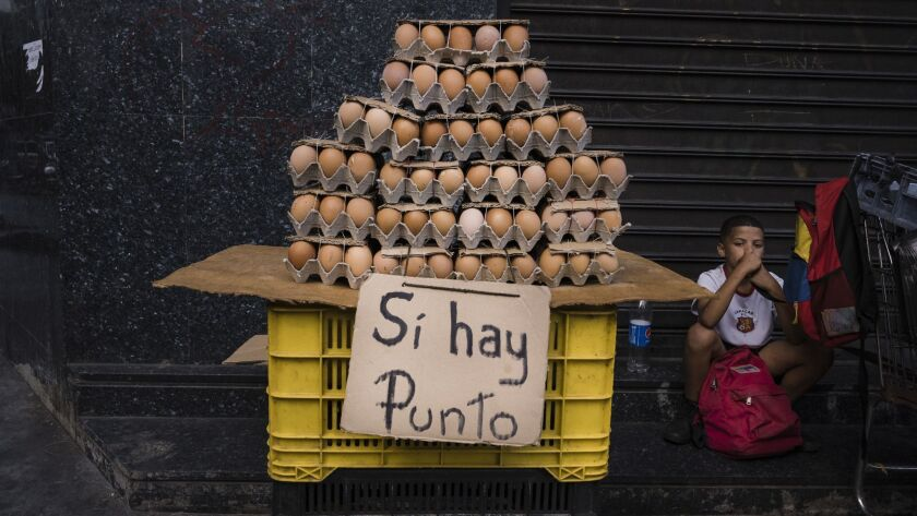 A Caracas street stand selling eggs displays a sign saying debit cards are accepted. Even small purchases are regularly paid with a debit or credit card due to cash shortages.