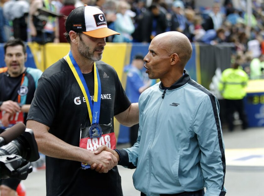 San Diego marathoner Meb Keflezighi, grand marshal of the 2019 Boston Marathon, congratulates El Cajon NASCAR driver Jimmie Johnson, left, after giving him his marathon participation medal. Johnson finished his first official marathon in just over three hours.