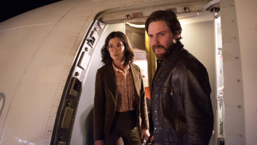 "Rosamund Pike and Daniel Brühl in the movie ""7 Days in Entebbe."""