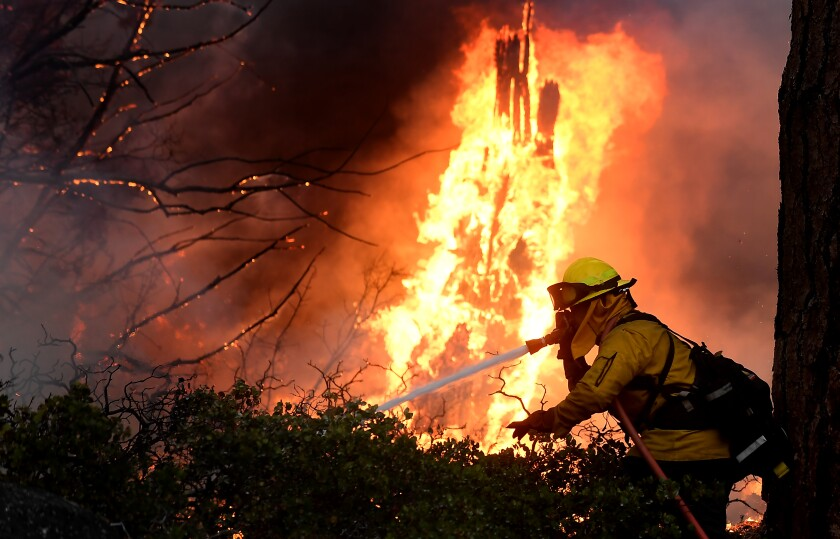 Firefighters battle the Caldor fire along highway 89 west of Lake Tahoe on Thursday.