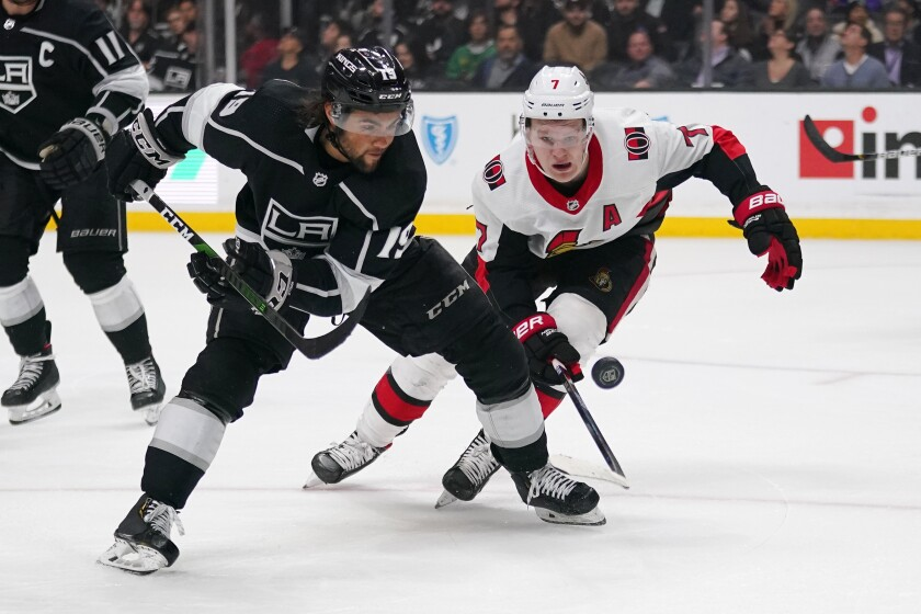 Kings left wing Alex Iafallo, left, goes after the puck along with Ottawa Senators left wing Brady Tkachuk during the third period on Wednesday at Staples Center.