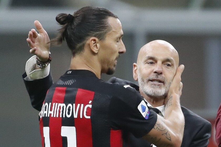 FILE - In this Saturday, Oc.t 17, 2020 file photo, AC Milan manager Stefano Pioli, right, congratulates Zlatan Ibrahimovic at the end of the Serie A soccer match between Inter Milan and AC Milan at the San Siro Stadium, in Milan, Italy. AC Milan coach Stefano Pioli has recovered from the coronavirus and will be back on the sidelines for Thursday's Europa League match against Celtic. Milan said on Wednesday that the latest tests carried out on Pioli and his assistant Giacomo Murelli were negative for COVID-19. (AP Photo/Antonio Calanni, File)