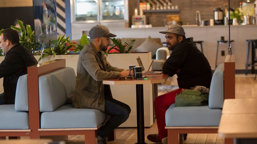 """Gibran Huerta, left, and Rick Zazueta have a business at WeWork called """"Lifestyle Group"""" that helps companies with branding through all kinds of media. They are sitting at a banquette in the third floor common area where WeWork members meet each over coffee and beer."""