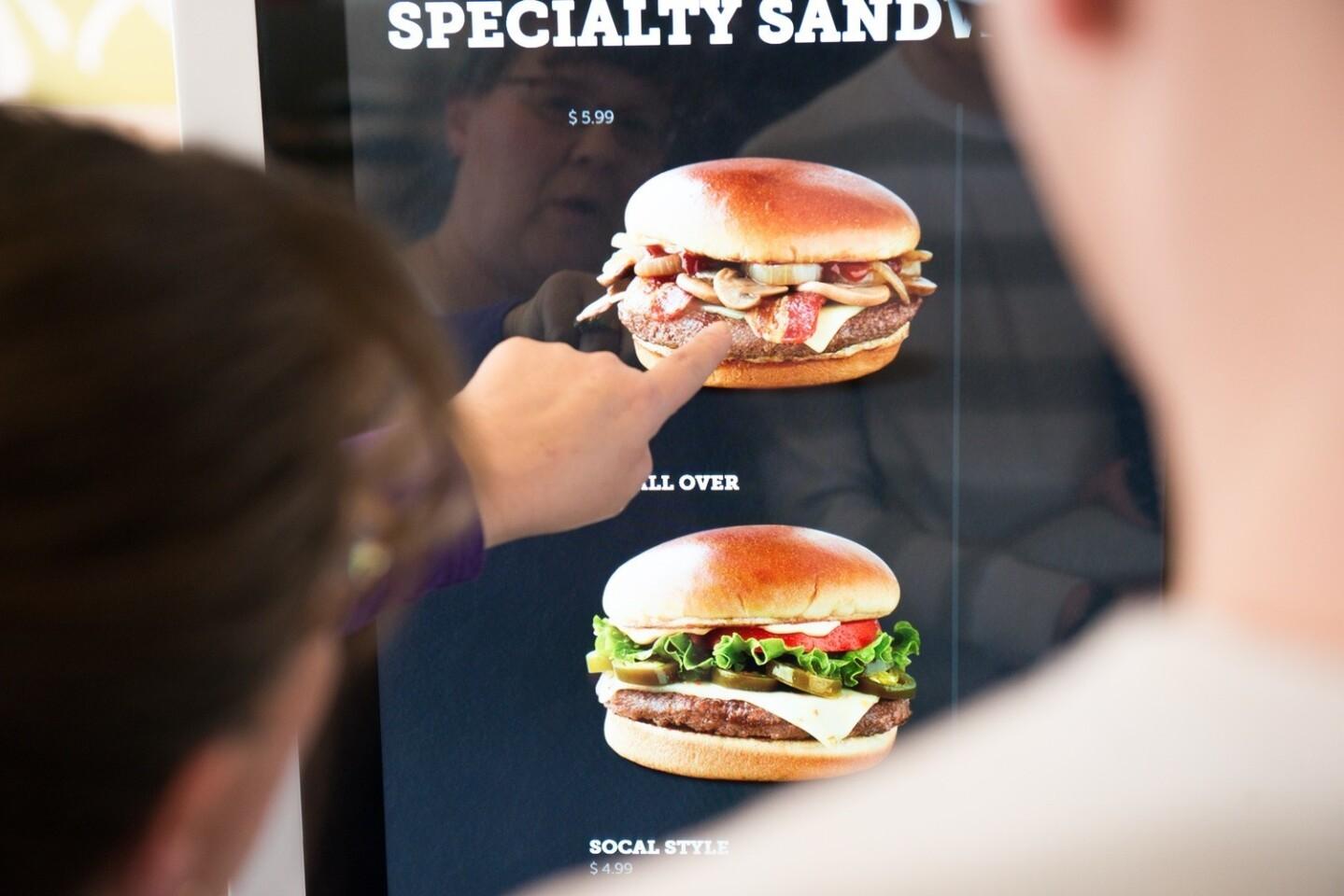 A customer uses McDonald's new Create Your Taste kiosk to order a burger.