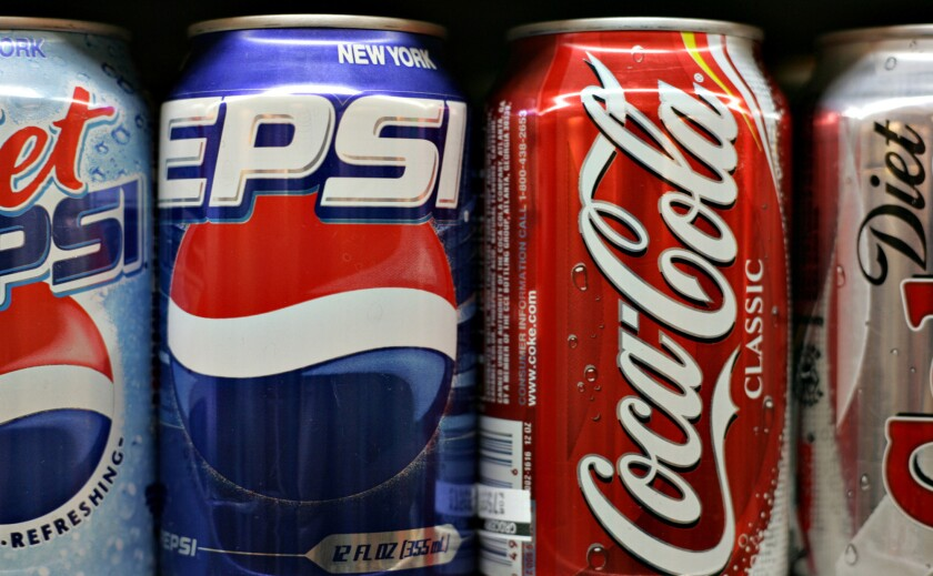 Pepsi and Coca-Cola products sit on display in a New York supermarket. Both companies have agreed to reduce their use of coolants that contribute to global warming.