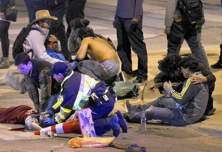 Victims are treated after being struck by a vehicle on Red River Street in downtown Austin, Texas, on Thursday. Two people were dead at the scene after a car drove through temporary barricades set up for the South by Southwest festival and struck a crowd of pedestrians.