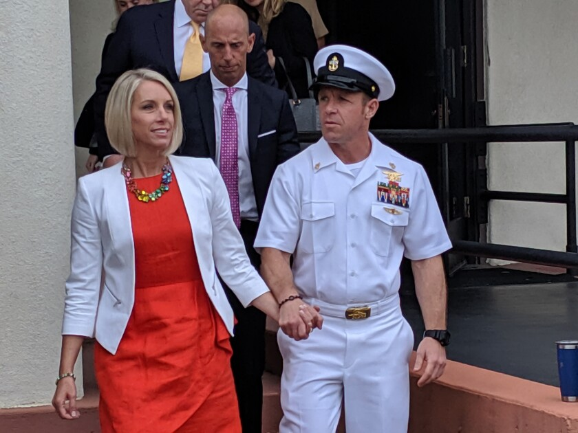 Navy Special Operations Chief Edward Gallagher leaves a military courtroom on Naval Base San Diego with his wife, Andrea Gallagher, during his court-martial in June. Walking out with them is Mark Mukasey, Gallagher's co-counsel and President Donald Trump's personal attorney.