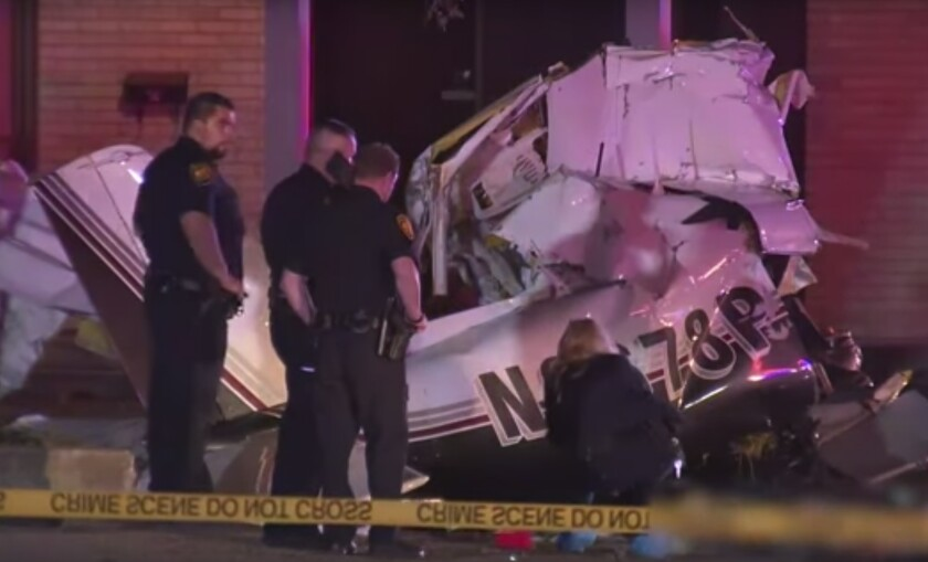 In this image made from video, police view the wreckage of plane crash Sunday, Dec. 1, 2019, in San Antonio, Texas. Officials say three people were killed when the single-engine plane crashed while attempting to land at San Antonio International Airport. San Antonio Fire Chief Charles Hood says the plane went down around 6:30 p.m. Sunday about a mile west of the airport. (KSAT via AP)